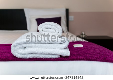 Close-up clean towels and soap in hotel room - stock photo