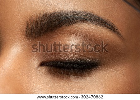 Close-up closed eye with make-up with brown eyebrows and black lashes - stock photo