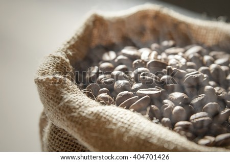 Close up coffee beans in jute bag on wooden table - stock photo