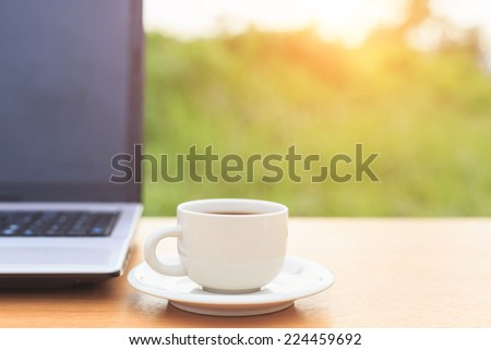 Close up coffee cup and laptop on the table in the morning