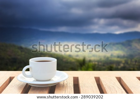 Close up coffee cup on wood table and view of mountain - stock photo