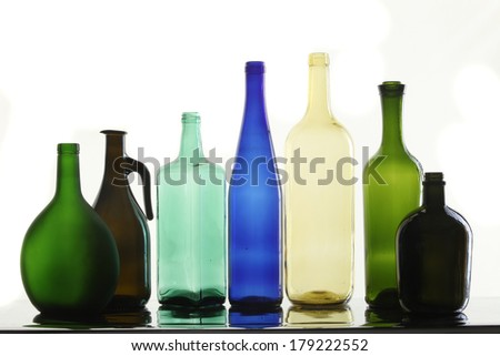 close-up collection of beautiful colored bottles of different shapes on a white background studio - stock photo