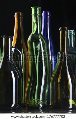 close-up collection of beautiful colored glass bottles on black background studio - stock photo