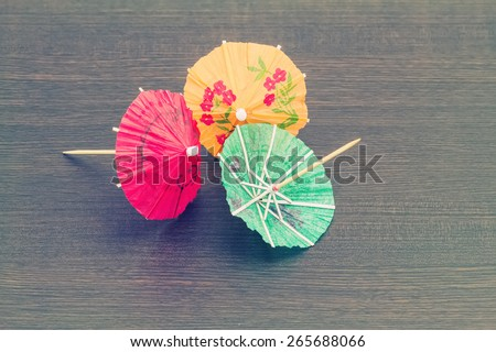 Close up colorful of many  cocktail umbrellas on black wooden  background process in vintage style - stock photo