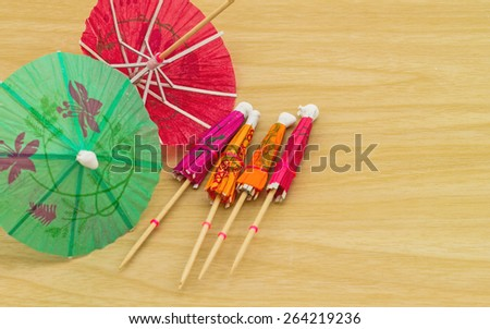 Close up colorful of many  cocktail umbrellas on white wooden background - stock photo