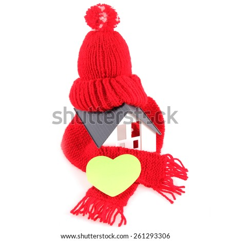 Close up Conceptual Red Wool Scarf Hat with Yellow Green Heart Shape, Emphasizing Copy Space, on Miniature Home. Isolated on White Background. - stock photo