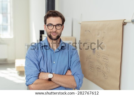 Close up Confident Young Bearded Businessman with Arms Crossing Over his Stomach, Standing Beside a Poster Paper on the Wall While Looking at the Camera. - stock photo