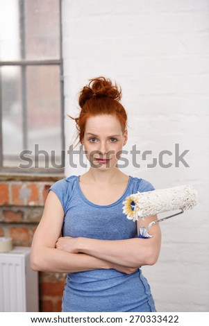 Close up Confident Young Woman Crossing her Arms Over her Stomach While Holding a Paint Roller and Looking at the Camera. - stock photo