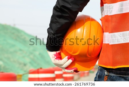 Close-up construction worker with safety vest holding hardhat on location site. Construction safety concept - stock photo