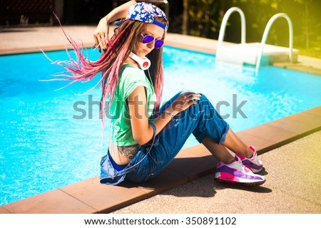 Close-up cool hipster girl with pink dreadlocks,wear floral cap big headphones,listens music enjoys holiday,colorful background,street fashion concept,casual punk outfit,music on earphones,tattoo girl - stock photo