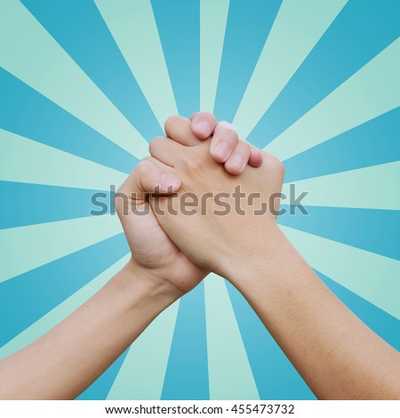 close up couple human handshake on sunburst blue color background:man hands shake for confident,success,victory,assurance concept:trust of humanity conceptual idea.action figure of powerful ideal - stock photo