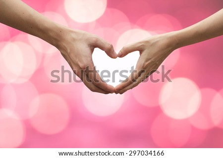 close up couple of male/female hands making heart on blurred pink bokeh background.passion in love concept,soft focus.world cancer day concept:intimacy of relationship people:encouragement /cheerful - stock photo