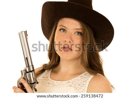 Close-up cowgirl holding big revolver serious expression - stock photo