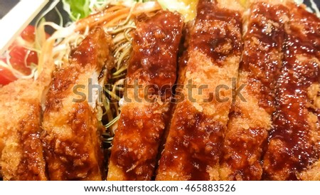 close up crispy fried pork and vegetable with sauce in black plate, tonkatsu , Japanese food