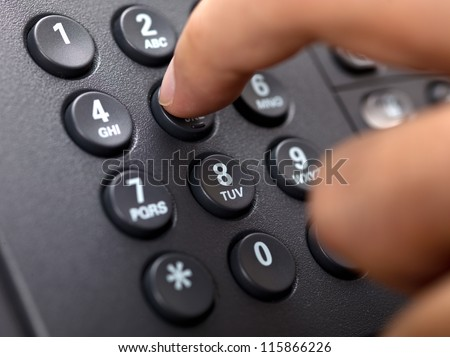 Close-up cropped image of a person dialing landlines phone. - stock photo
