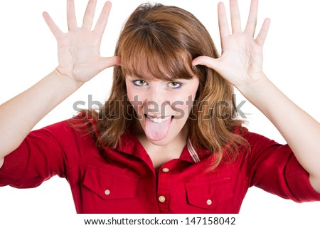 Close-up, cropped portrait of a woman sticking her tongue out with thumbs at her temples, isolated on white background - stock photo