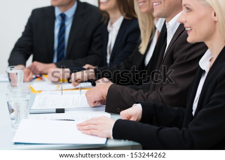 Close up cropped view of an attractive businesswoman in a meeting with the hands of her diverse coworkers visible in the background - stock photo