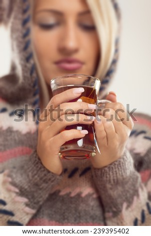 Close-up cup of tea held by the hands of girl, with a face out of focus, dressed in wool sweater with hood. - stock photo