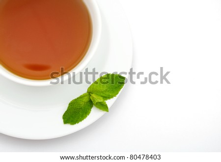 Close-up cup of tea with mint leaves over white background