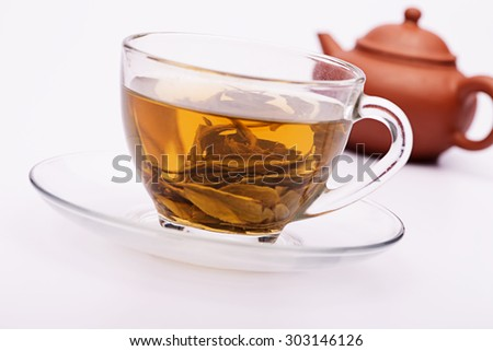 Close up Cup with green tea and green leaves over white background - stock photo