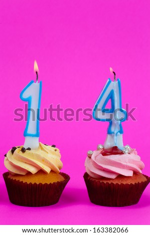 Close up cupcakes with digri candles on colored background