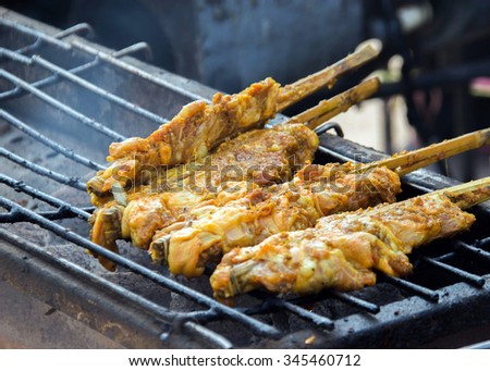close up curry chicken with wood stick on grill barbecue smoke - stock photo
