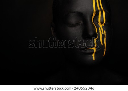 close-up dark portrait of woman in black paint with yellow smudges isolated on black - stock photo