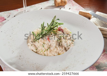 Close up Delicious italian risotto with white mushrooms, tomatoes and parsley decorated with rosmary and parmesan on the white plate - stock photo