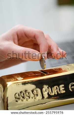 close up detail hand dropping a coin in gold ingot shaped piggy bank money box - stock photo