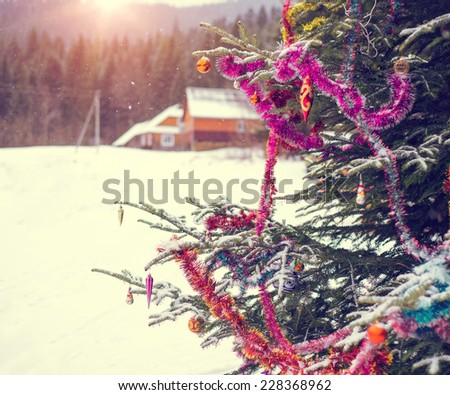 Close up detail of a decorated Christmas tree with bar balls in the wilderness nature of the snow mountains with a wooden house during Xmas winter season day on the sunset. Instagram style filter. - stock photo