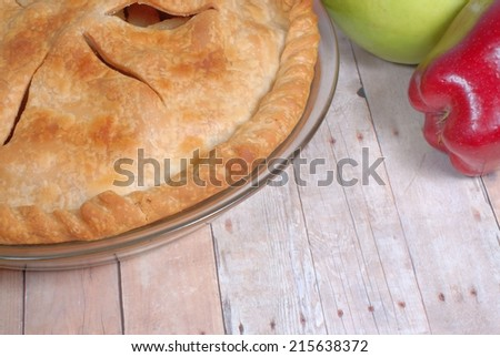 Close up detail of a freshly baked apple pie on rustic wooden table with apples around. The crust is golden brown. The pie is in a clear glass pan. The horizontal image with copy space on table top - stock photo