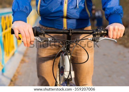 Close up detail of a man riding a bicycle along a pathway approaching the camera with focus to his hands on the handlebars - stock photo