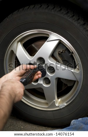 Close-up detail of a mechanic tightening or loosening the lugs of an aluminum rim. - stock photo