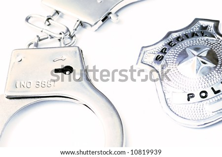 close-up detail of a police metal badge and handcuffs - stock photo