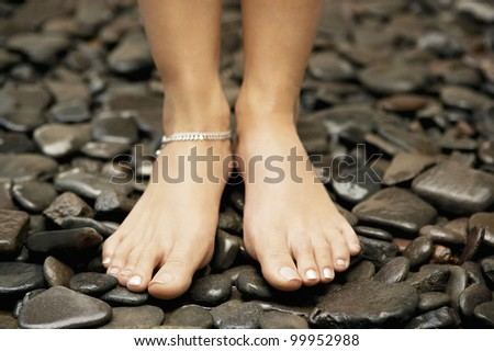 Close up detail of a woman's feet wearing an anklet and standing on black stones.