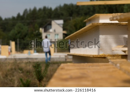Close up detail of an insulated wall panel lying on a construction site with the workers busy working on the house in the background - stock photo