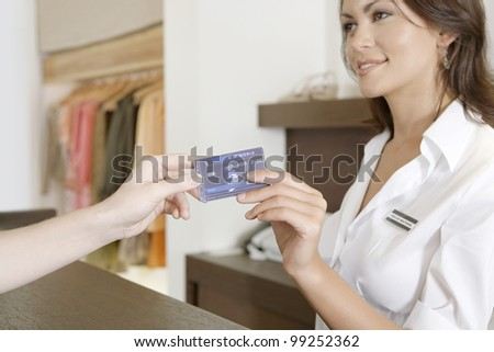 Close up detail of client's hand handing over credit card to a smiling store attendant.