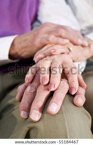 Close-up detail of hands of senior couple touching and resting on knee - stock photo