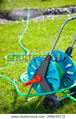 Close up detail of hose for watering the garden on the green grass (sunlight, colorful image, gardening concept) - stock photo