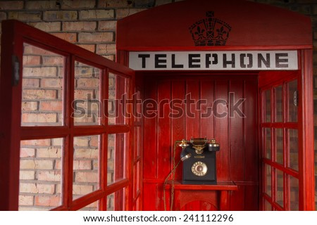 Close Up Detail of Red Public Telephone Booth with Old Fashioned Telephone Inside and Open Door - stock photo
