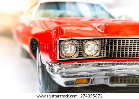 Close Up Detail of Shiny Red Classic Car with Focus on Headlights and Hood. - stock photo