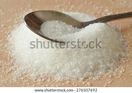Close-up detail of spoon in heap of white granulated crystal sugar on wooden desk - stock photo