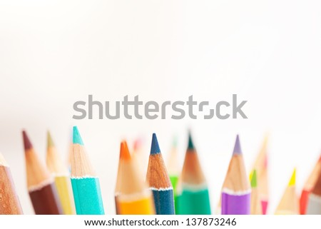 Close up detail of the tips of a bunch of colored school art pencils pointing upwards, isolated on a white background. - stock photo