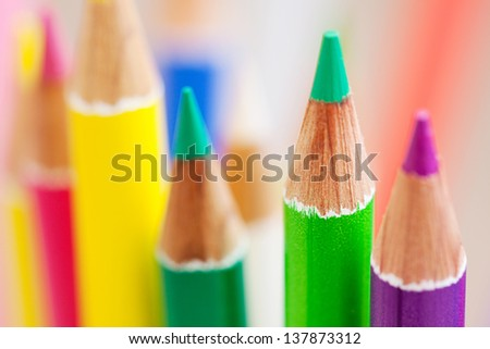 Close up detail of the tips of a bunch of colorful school art pencils pointing upwards with texture and color. - stock photo