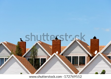 Close up detail of town house rooftops with chimneys against blue shy. - stock photo