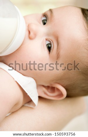 Close up detail portrait of a new baby girl in her mothers arms drinking milk from a baby bottle and turning to look at camera, feeling calm and relaxed. Home interior. - stock photo