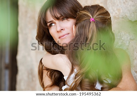 Close up detail portrait of an attractive mother and her young daughter hugging and cuddling in a holiday home garden during a sunny summer day, outdoors. Loving family outdoors lifestyle. - stock photo