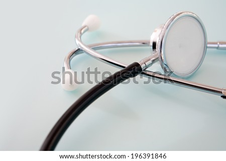 Close up detail still life view of a doctor stethoscope laying on a plain blue background space on a hospital table, interior. Health and medical equipment and insurance icon with no people.