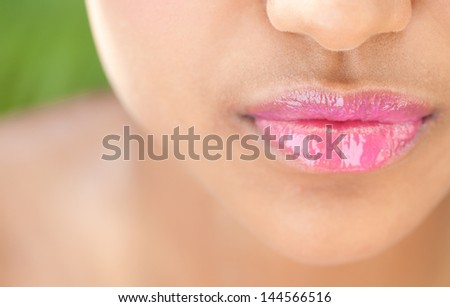 Close up detail view of a beautiful young woman's mouth with perfect lips wearing glossy pink lipstick against a nature green background.