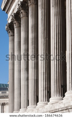 Close up detail view of a centenary old stone building with aligned decorative columns and vertical carvings. Grand and luxurious classic architecture still life of London city, sunny exterior.